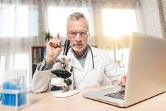 Doctor sitting at desk in office with microscope and stethoscope. Man is looking in microscope. stock photography