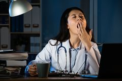 Doctor sitting at desk and yawning in hospital. Overworked female doctor sitting at the desk and yawning at hospital. beautiful mixed race asian chinese woman Royalty Free Stock Photo