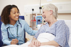 Doctor Sitting By Female Patient's Bed In Hospital Stock Image
