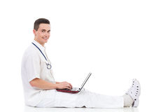 Doctor sitting on the floor with laptop, Side view. Royalty Free Stock Image