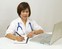 Doctor sitting at her desk in her office Royalty Free Stock Photos