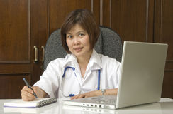 Doctor sitting at her desk in her office Royalty Free Stock Image