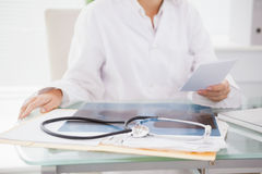 Doctor sitting at her desk with laptop and files Royalty Free Stock Photography
