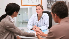 Doctor sitting at her office speaking with patients stock video