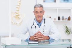 Doctor sitting at his desk smiling at camera Stock Image