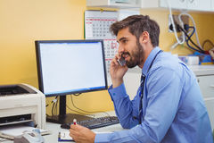 Doctor sitting at his desk and talking on phone Royalty Free Stock Images