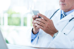 Doctor sitting at his desk and texting Stock Images