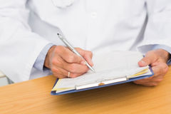 Doctor sitting at his desk writing on clipboard Royalty Free Stock Images