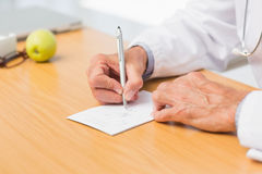 Doctor sitting at his desk writing out a prescription Royalty Free Stock Photography