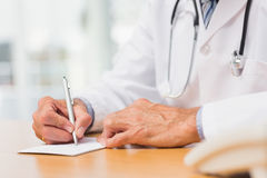 Doctor sitting at his desk writing a prescription Stock Photo