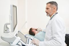 Doctor sitting, looking at screen, doing diagnosis of neck. royalty free stock images