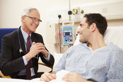 Doctor Sitting By Male Patient's Bed In Hospital Stock Photo