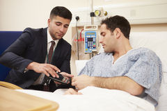 Doctor Sitting By Male Patient's Bed Using Digital Tablet Royalty Free Stock Images