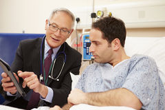 Doctor Sitting By Male Patient's Bed Using Digital Tablet Stock Photos