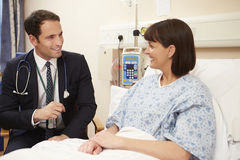 Doctor Sitting By Male Patient's Bed Using Digital Tablet Royalty Free Stock Photography