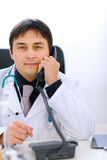 Doctor sitting at office table and speaking phone Royalty Free Stock Images