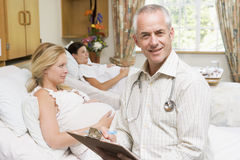 Doctor sitting by pregnant women holding chart Stock Photography