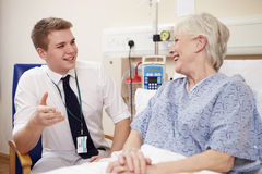Doctor Sitting By Senior Female Patient's Bed In Hospital Stock Image