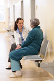Doctor sitting with senior patient Stock Photo
