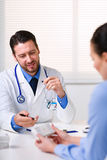 Doctor sitting at table in front of patient Stock Photos