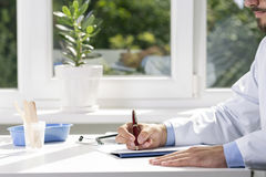 Doctor sitting by the table and writing a document Royalty Free Stock Images