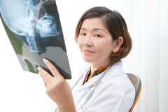 Doctor sitting in working room and reading data fr Stock Photos