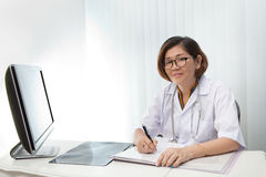 Doctor sitting in working room and reading data fr Stock Images