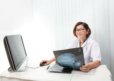 Doctor sitting in working room and reading data fr Stock Photography