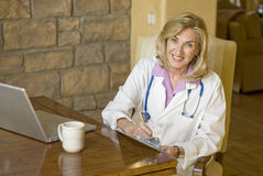 Doctor sitting and writing at her desk Royalty Free Stock Photography
