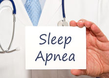 Doctor with Sleep Apnea sign. Doctor holding Sleep Apnea sign in his hand stock photo