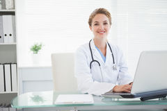 Doctor smiling as she types Stock Images