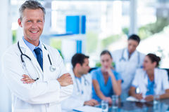 Doctor smiling at camera with colleagues behind Stock Images
