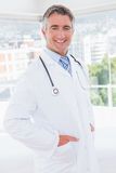 Doctor smiling at camera with hands in pockets Stock Images