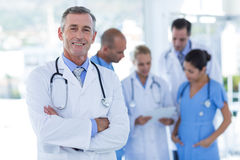 Doctor smiling at camera while his colleague discussing Stock Image