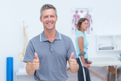 Doctor smiling at camera while his patient standing with crutch Stock Photography