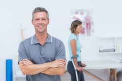 Doctor smiling at camera while his patient standing with crutch Stock Image