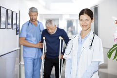 Doctor Smiling While Colleague Assisting Senior Man With Crutche. Portrait of confident doctor smiling while colleague assisting senior men with crutches in Royalty Free Stock Photo