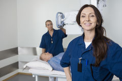 Doctor Smiling While Colleague Taking Patient's Xray Royalty Free Stock Photography