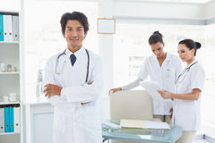 Doctor smiling in front of work colleagues Royalty Free Stock Photography