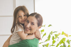 Doctor and a smiling girl patient. Beautiful little girl hugging women doctor Royalty Free Stock Photography