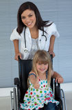 Doctor and Smiling girl on a wheelchair Stock Images