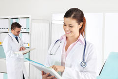 Doctor smiling with medical documents Stock Photography