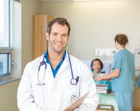 Doctor Smiling While Nurses Examining Patient In Stock Images