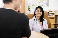 Doctor Smiling With Patient In Foreground At Clinic royalty free stock photography