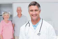 Doctor smiling with senior couple in background at clinic Royalty Free Stock Images