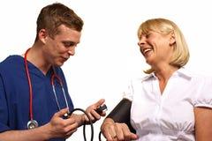 Doctor som kontrollerar blodtryck royaltyfri fotografi