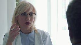 Doctor som talar med tålmodig stock video