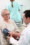 Doctor som tar blodtryck Royaltyfria Bilder
