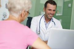 Doctor sonriente con el paciente Foto de archivo