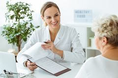 Doctor sonriente durante exámenes médicos imagen de archivo
